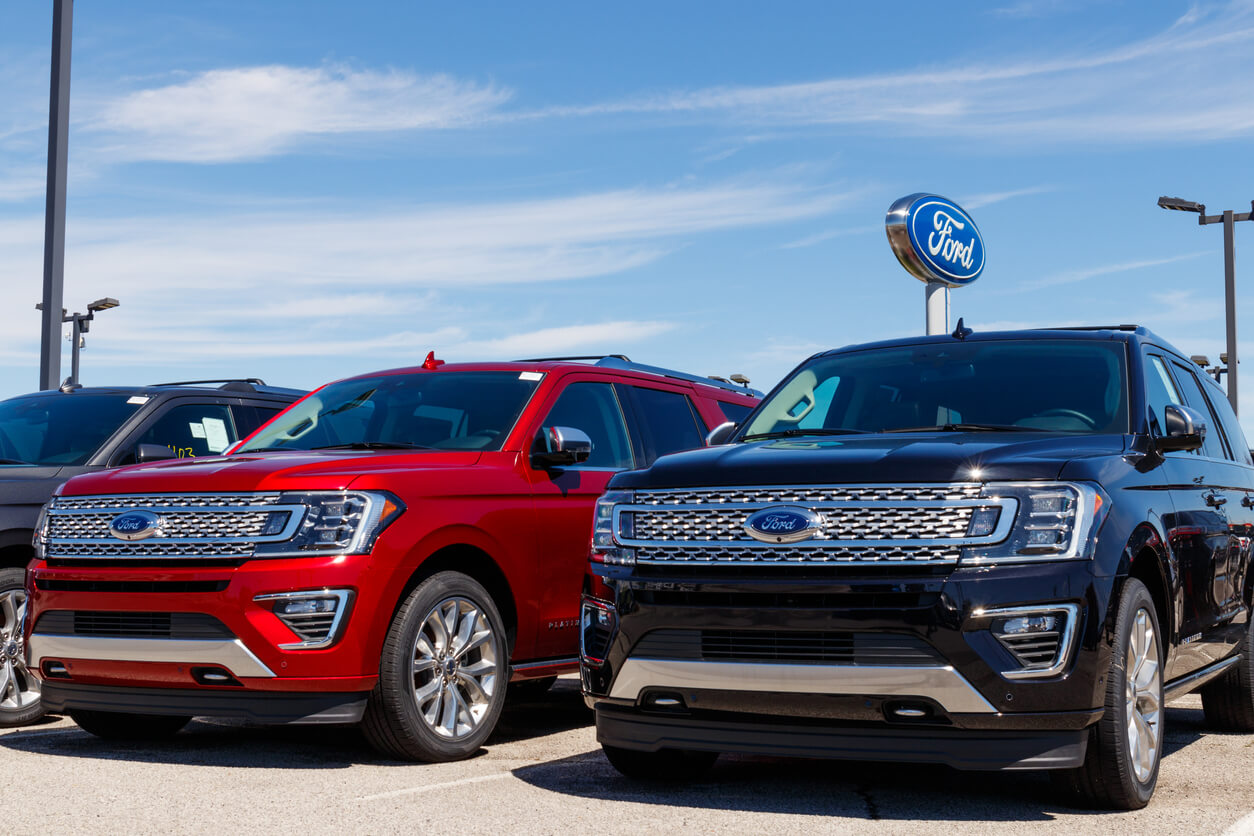 Ford SUVs and trucks in dealership parking lot.